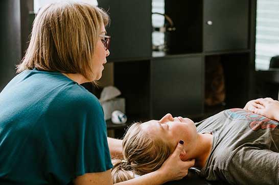 Chiropractor Salado TX Dr. Allyn Crain Examining Patients Neck